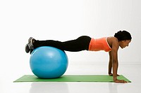 Profile of African American woman doing push ups with feet on exercise ball