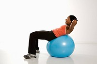 Side view of African American woman balancing on exercise ball doing crunches
