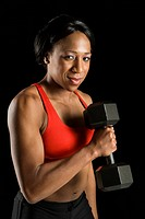 African American young adult woman holding dumbbell and looking at viewer