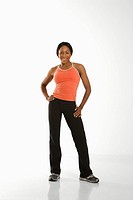 African American young adult woman in athletic wear smiling at viewer with hands on hips (thumbnail)