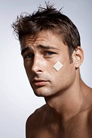 Mid adult man with adhesive plaster on cheek
