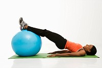 Profile of African American woman stretching on mat with legs on exercise ball