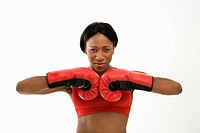 African American young adult woman wearing boxing goves with fists together