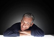 Mature man leaning on table and laughing portrait