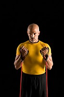 Mid adult multiethnic man wearing yellow exercise shirt exercising with stretch band while looking at viewer