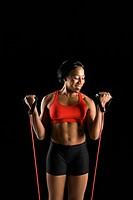 Smiling African American young adult woman exercising with resistance tube