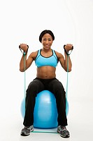 African American young adult woman sitting on exercise ball using resistance tube