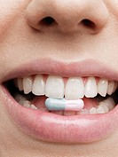 Woman holding vitamin pill in teeth