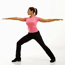 Side view of mid adult multiethnic woman wearing exercise clothing standing in yoga warrior pose