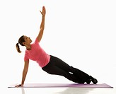 Mid adult multiethnic woman wearing exercise clothing holding yoga pose and stretching