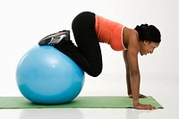Profile of African American woman working out using an exercise ball