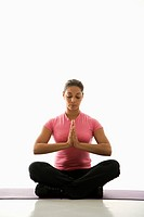 Mid adult multiethnic woman sitting in Namaste position on exercise mat with eyes closed and hands at heart center