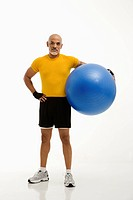 Mid adult multiethnic man standing and holding blue exercise ball looking at viewer
