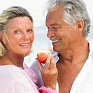 senior couple on beach holding apple