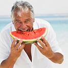Senior man on beach eating water melon