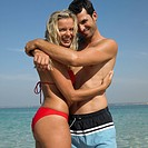 Couple embracing on beach, laughing