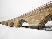 Scene of stone bridge over over snow covered road