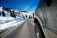Perspective shot of SUV driving down road in snowy Colorado during winter