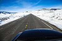 Perspective shot of car driving down road in snowy Colorado during winter