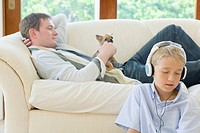 Father and son with Chihuahua in living room, father lying on couch and son listening to music
