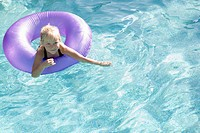 Girl in an inner tube in swimming pool, smiling