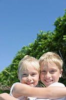 Portrait of girl and boy smiling and looking at camera, hugging (thumbnail)