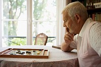 Senior caucasian man playing a board game, Side View, Differential Focus