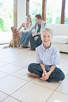 Family with Golden Retriever in living room, portrait for son, looking at camera
