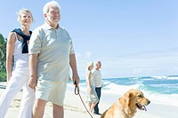 Senior couples and Golden Retriever on beach, man standing with leash