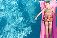 Boy lying on pool raft in swimming pool, copy space