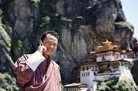 Bhutanese man with cell phone, Taktshang Goemba Tiger´s Nest Monastery, Paro, Bhutan, Asia