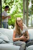 Caucasian woman relaxing and stroking a cat, Front View, Side View, Differential Focus