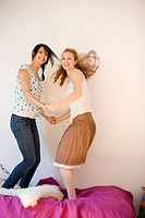 Two caucasian women jumping on a bed, Side View