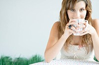 Young Woman Drinking Coffee, Looking at Camera (thumbnail)
