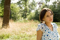 Image of a Young Adult Woman Sitting Outside in a Field, Looking Sideways, Differential Focus, France
