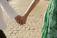 Young couple walking hand in hand, front view, close up