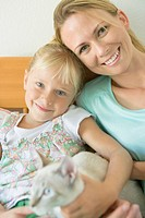 Portrait of girl and mother with cat, smiling and looking at camera