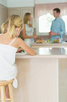 Family in kitchen, girl drawing at kitchen counter