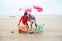Couple pointing and laughing under beach umbrella
