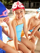 Girl in swimming costumes sitting on bench portrait