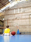 Boy sitting in basketball court rear view