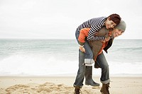 Man giving woman piggyback on beach (thumbnail)