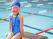 Girl wearing swimming goggles by pool portrait