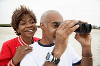 Couple using binoculars at beach