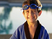 Boy wearing swimming goggles and gown portrait