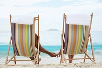 Couple on lounge chairs, holding hands rear view, St. John, US Virgin Islands, USA