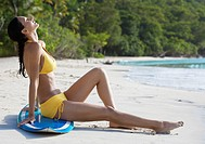 Young woman sunbathing on surfboard at beach, St. John, US Virgin Islands, USA