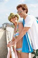 Young couple in beach attire leaning against railings
