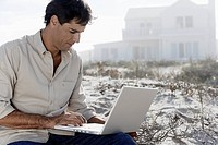 Mature man using laptop at beach