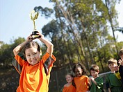Girl holding trophy, soccer team in background portrait
